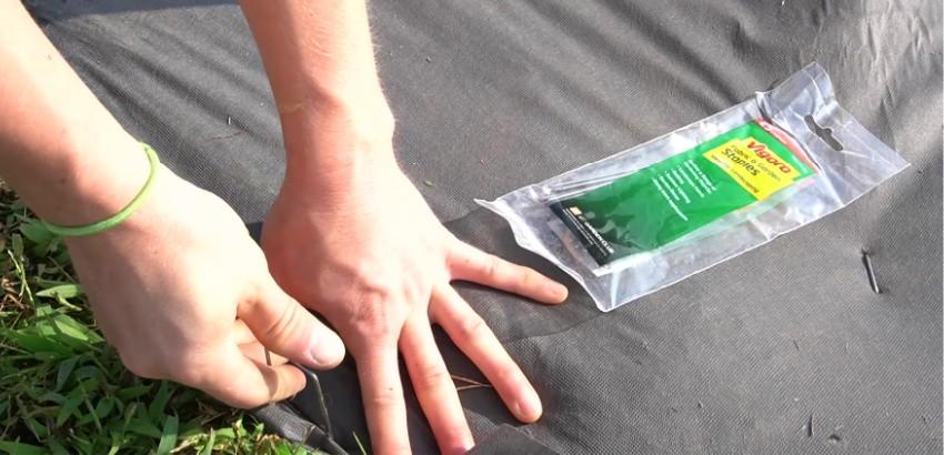Securing weed barrier around outdoor eye sore with Vigoro garden staples
