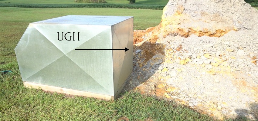 Ugly well house cover next to large rock pile