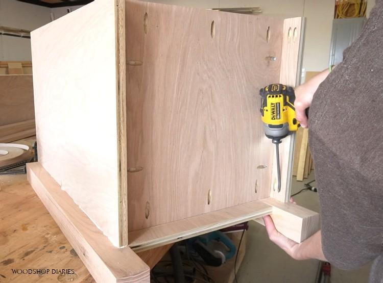 Screwing bottom panel into desk cabinet using pocket hole screws