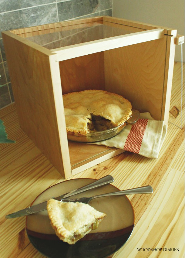 DIY Scrap Wood and plexiglass pie and cake carrier display box with front piece open and a slice of apple pie cut