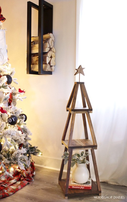 Stackable Christmas tree shelf set up next to Christmas tree with decor sitting on it