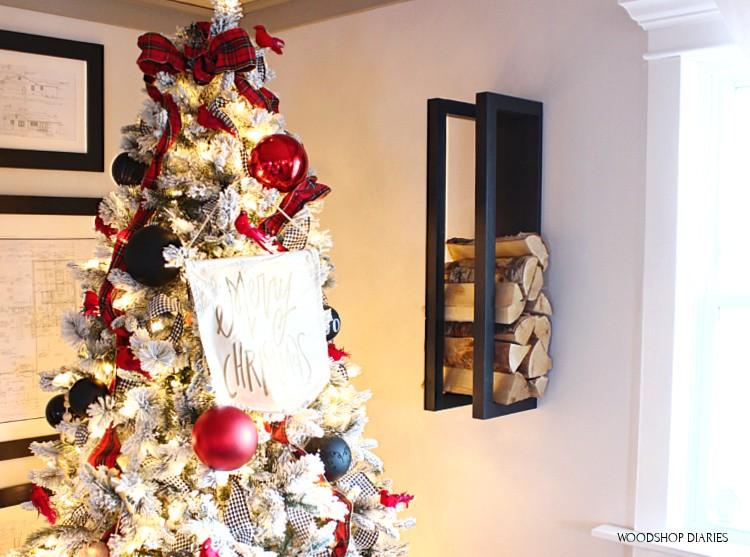 DIY scrap wood firewood rack hanging on wall next to Christmas tree