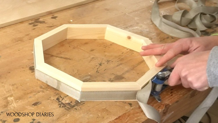 Using a ratchet strap clamp to assemble tiered tray edges