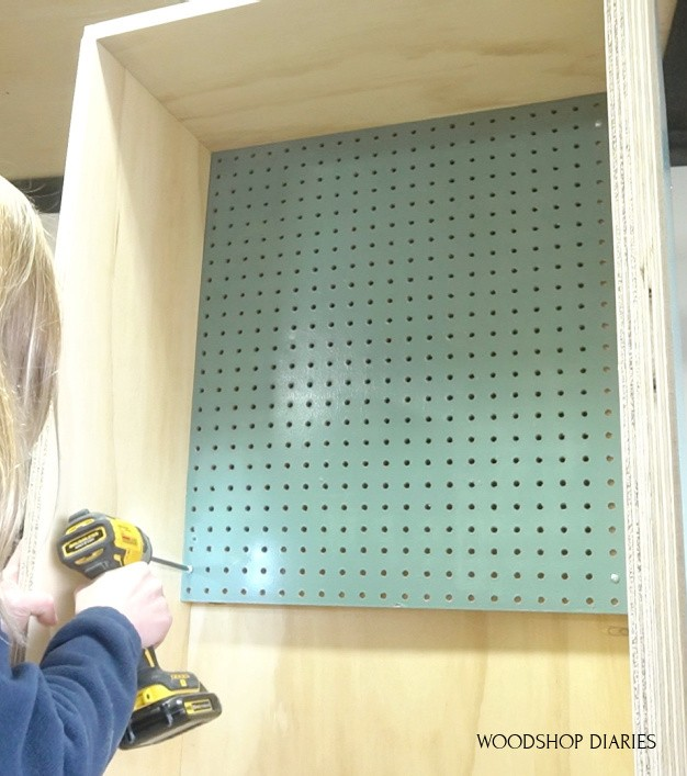 Screw peg board panel onto cabinet