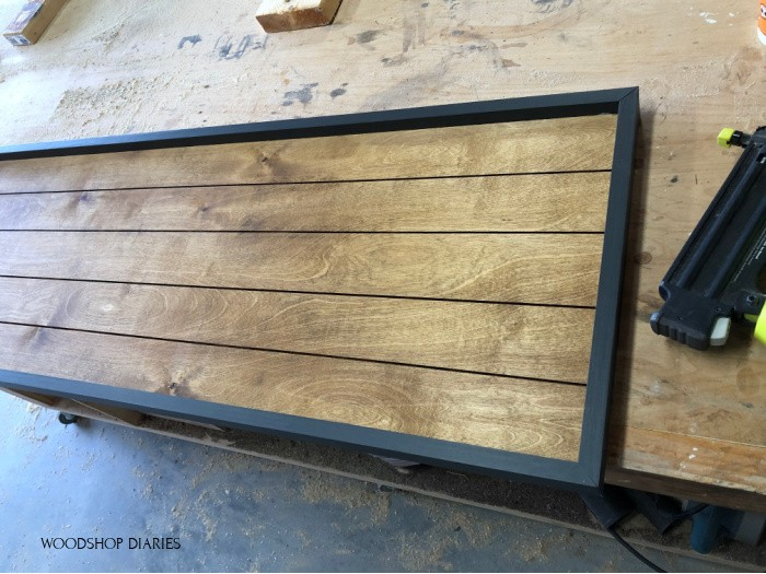 Stained back panel with black 1x2 frame nailed in place along sides