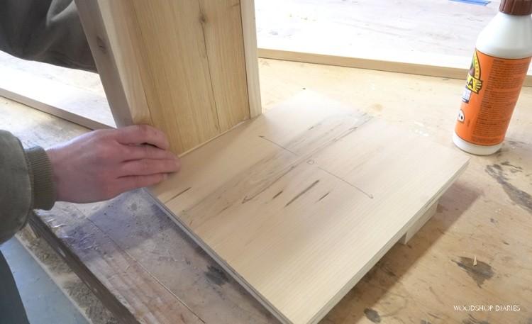 Using spacer block to attach bottom shelf to ladder