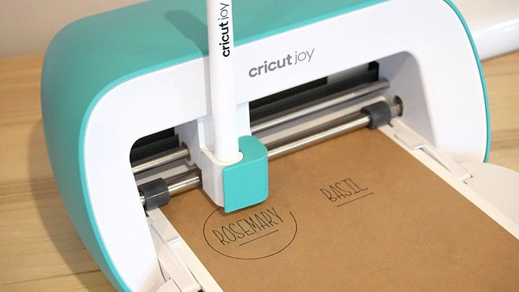 Close up of Cricut Joy drawing name stickers on writable paper