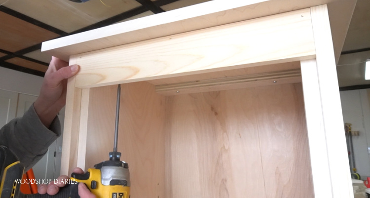 Screwing top plywood panel onto top of linen cabinet frame