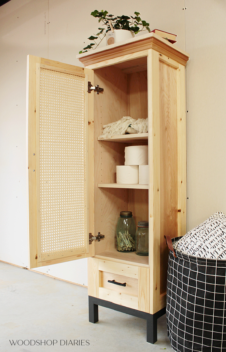 Finished DIY cane door linen cabinet or tall pantry cabinet with door open and adjustable shelves inside