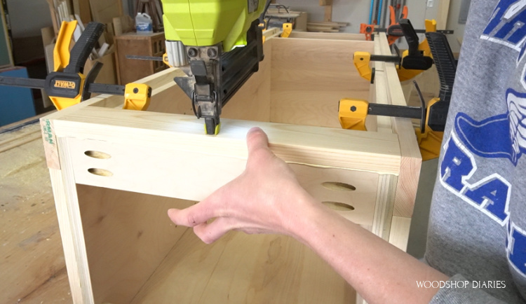 Using brad nailer to attach front face frame piece to linen cabinet