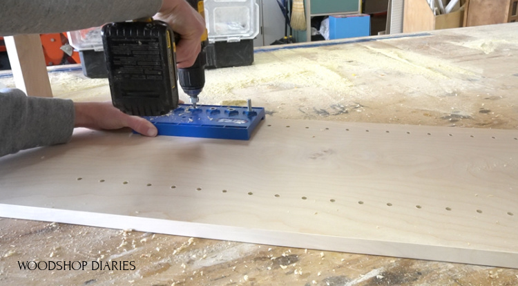 Using a shelf pin jig to drill shelf pin holes into cabinet sides