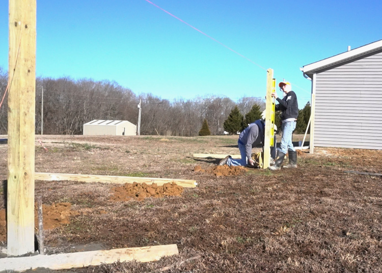 Installing fence posts into post holes and leveling with concrete mix