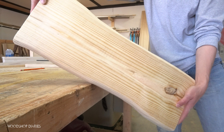 Shara Woodshop Diaries holding DIY faux live edge pine board with edges carved using angle grinder