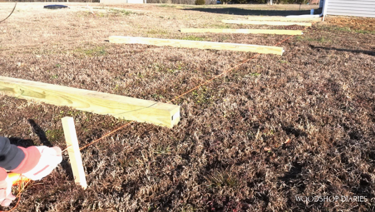 Fence posts laid out on ground with string pulled to keep straight
