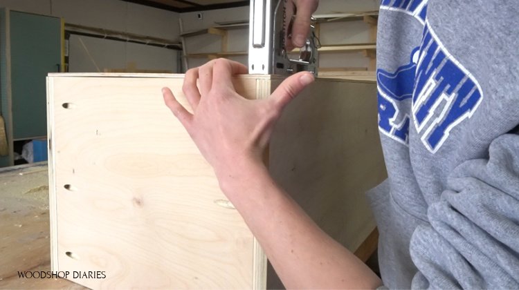 Stapling back panel in place on linen cabinet