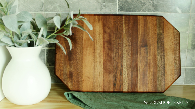 DIY Mahogany cutting board made from old front door leaning against tile backsplash on countertop