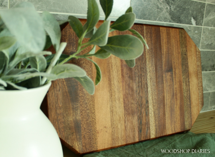 Finished cutting board on countertop leaning against backsplash