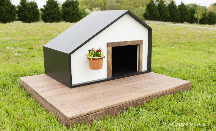 Black and White modern style dog house on wood deck in yard with flower hanging on front