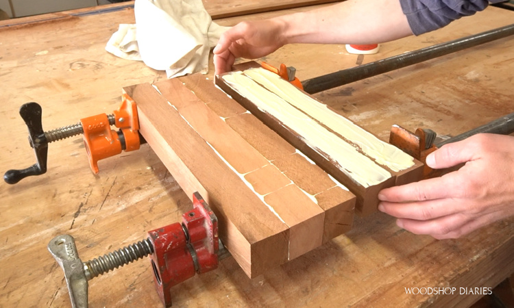 Gluing up section of cutting board in pipe clamps with wood glue