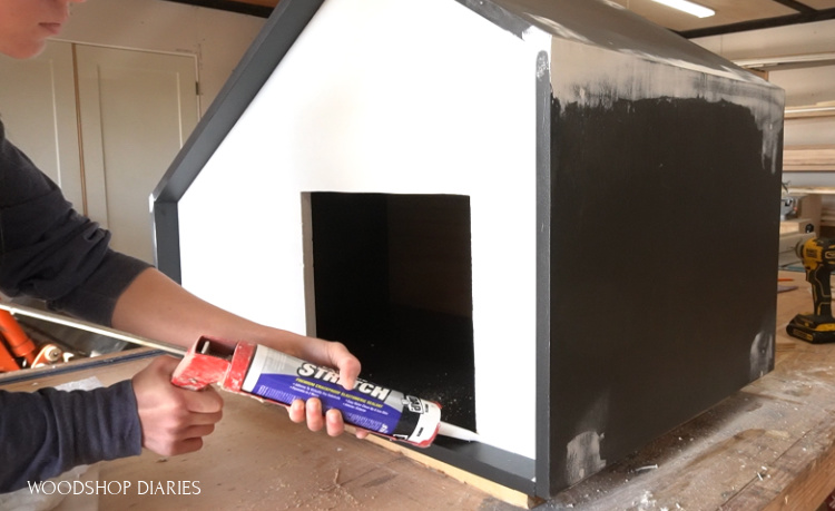 Shara Woodshop Diaries caulking along joints in DIY outdoor dog house to seal it