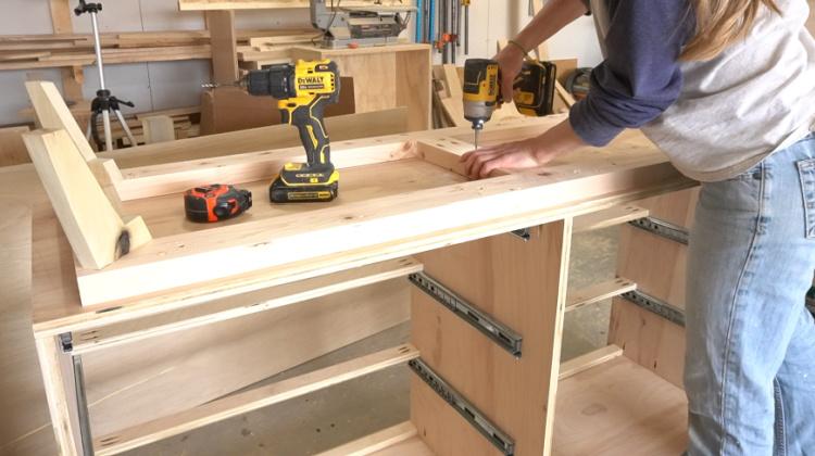 Shara Woodshop Diaries screwing base frame into bottom of dresser box