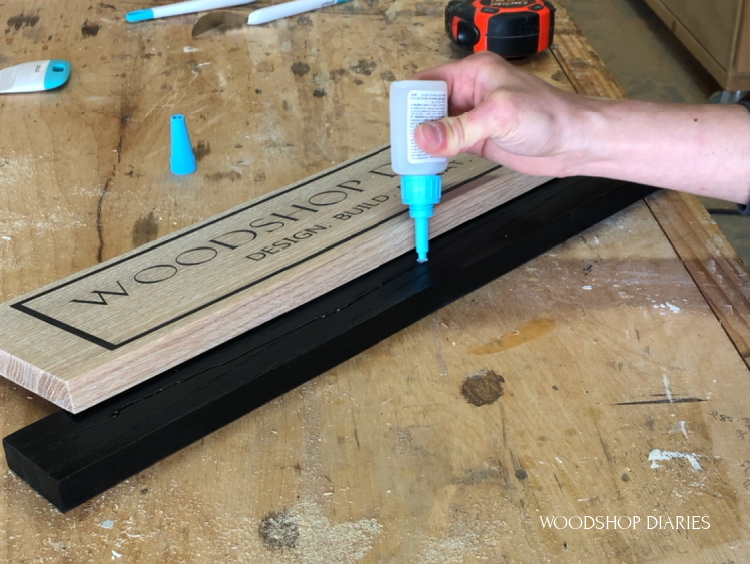 Applying super glue to base plate to attach wooden sign board