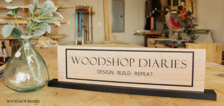 Woodshop Diaries custom sign on base plate sitting on workbench in workshop