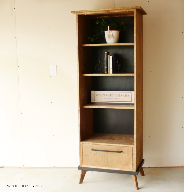 Black and wood mid century modern DIY bookcase cabinet with adjustable shelves and drawer against plan white wall
