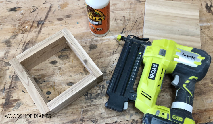 Nail gun and wood glue on workbench used to assemble small square box for lantern base
