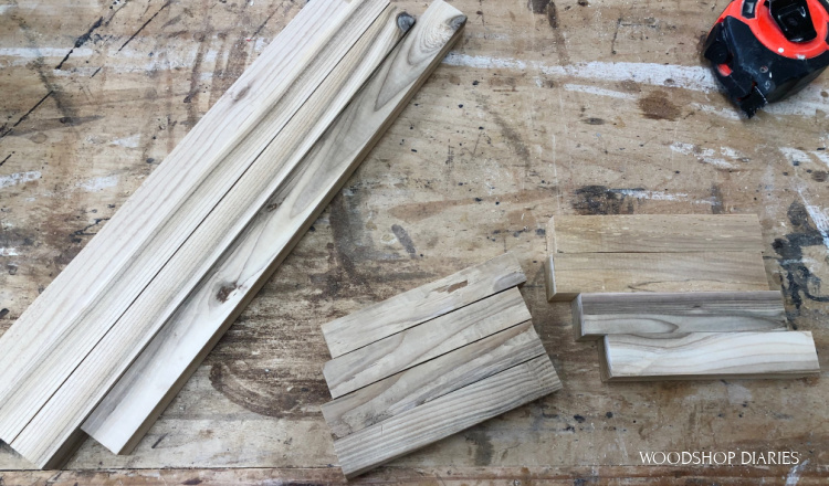 Pieces cut and laid out on workbench to assemble scrap wood lantern frame