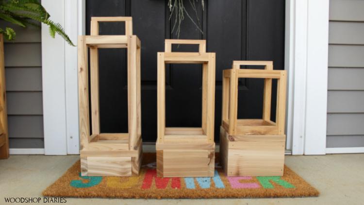 Three sizes of simple outdoor scrap wood lantern sitting on rug in front of front door