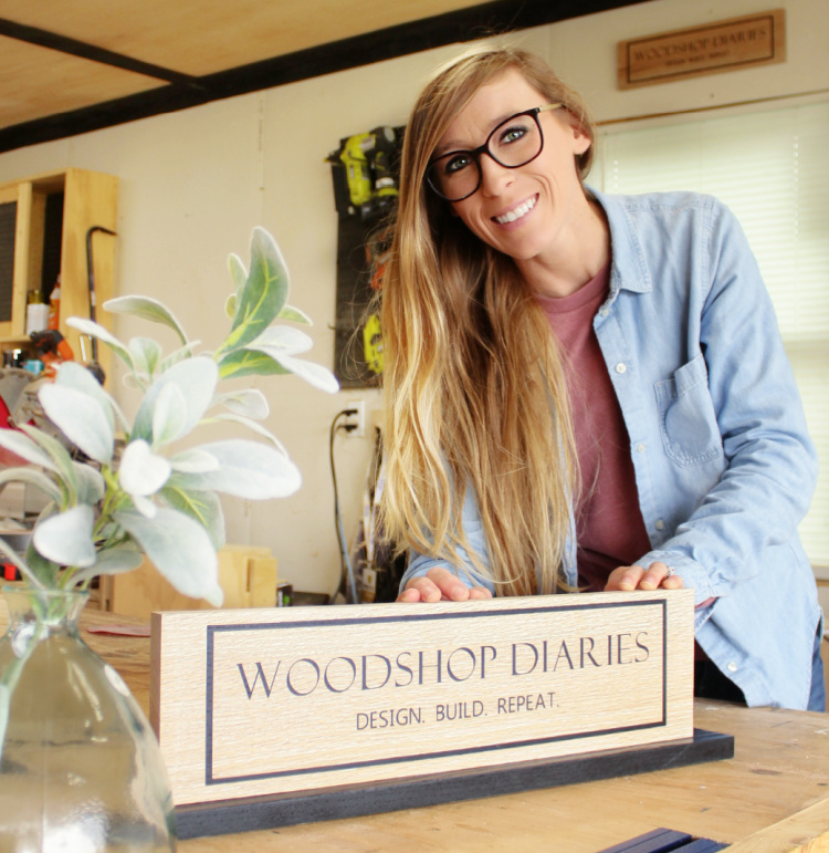 Shara Woodshop Diaries with DIY custom wooden signs in workshop--one on wall and one on base plate sitting on workbench
