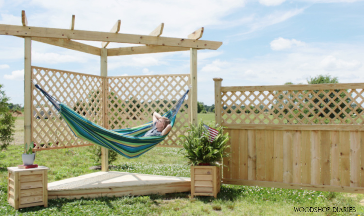 Shara lying in hammock on hammock stand over floating deck with privacy lattice