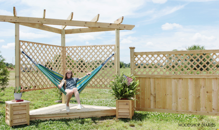 Shara Woodshop Diaries sitting in hammock on hammock stand with pergola