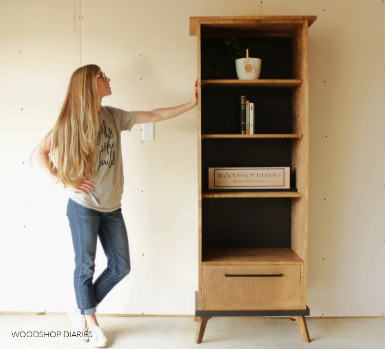 Shara Woodshop Diaries standing next to black and wood modern style bookcase cabinet with shelves and drawer