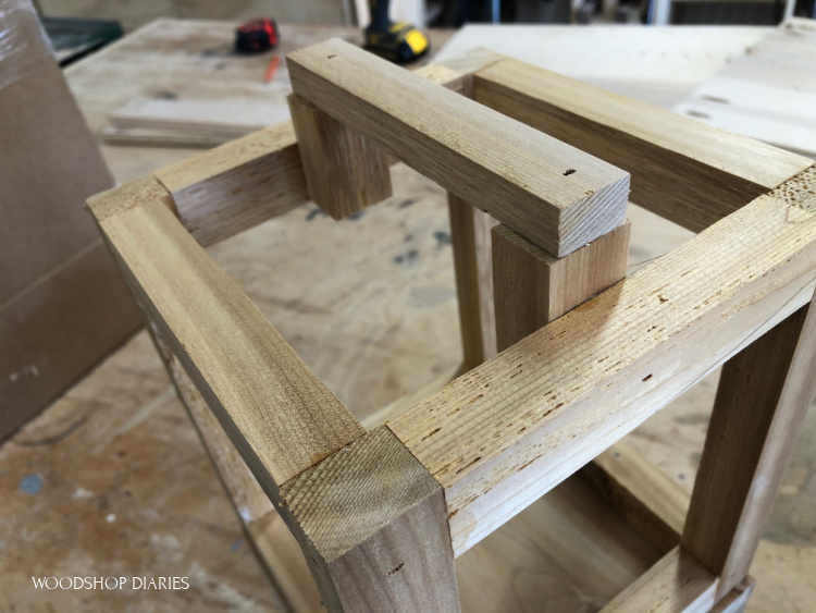 Close up of scrap wood handle glued and nailed to top of lantern frame