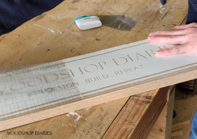 Remove transfer tape from vinyl stencil on oak board