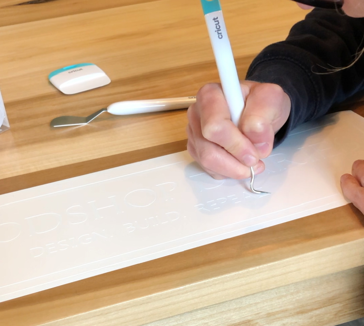 Using picker tool to remove lettering from vinyl stencil