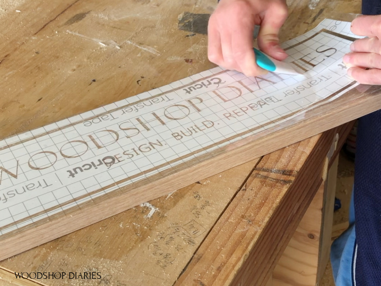 Smoothing out stencil onto wooden sign board