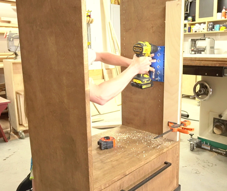 Shara drilling shelf pin holes into cabinet sides