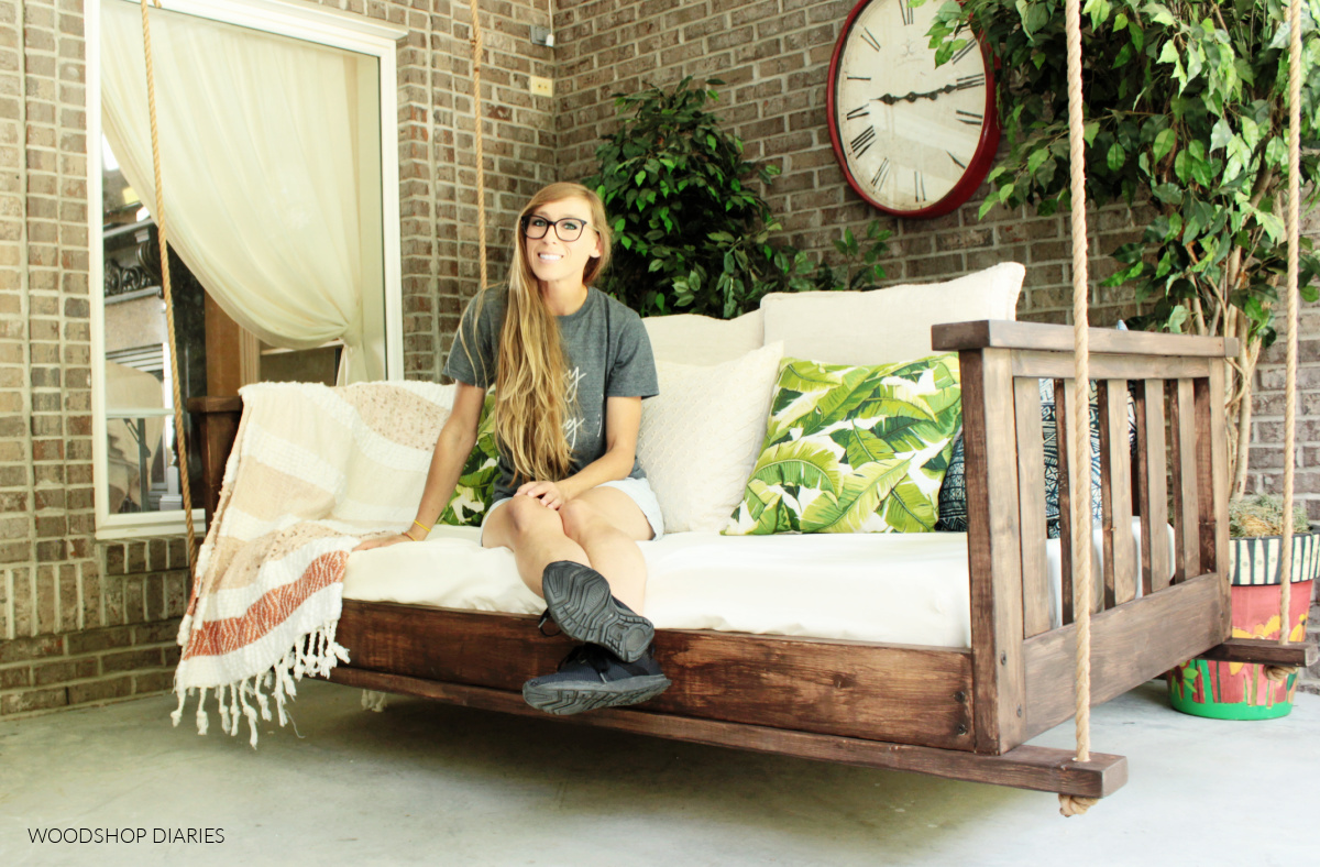 Shara Woodshop Diaries sitting in dark stained DIY hanging wooden porch swing bed with brick background
