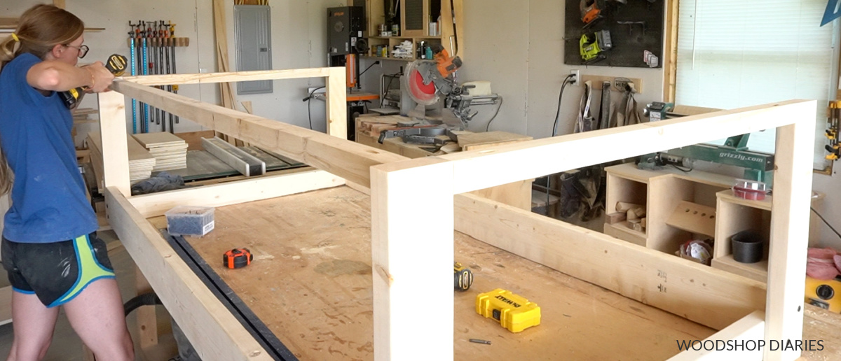 Wide picture of Shara Woodshop Diaries in workshop installing 2x2 supports at top of swing frame using pocket holes and screws