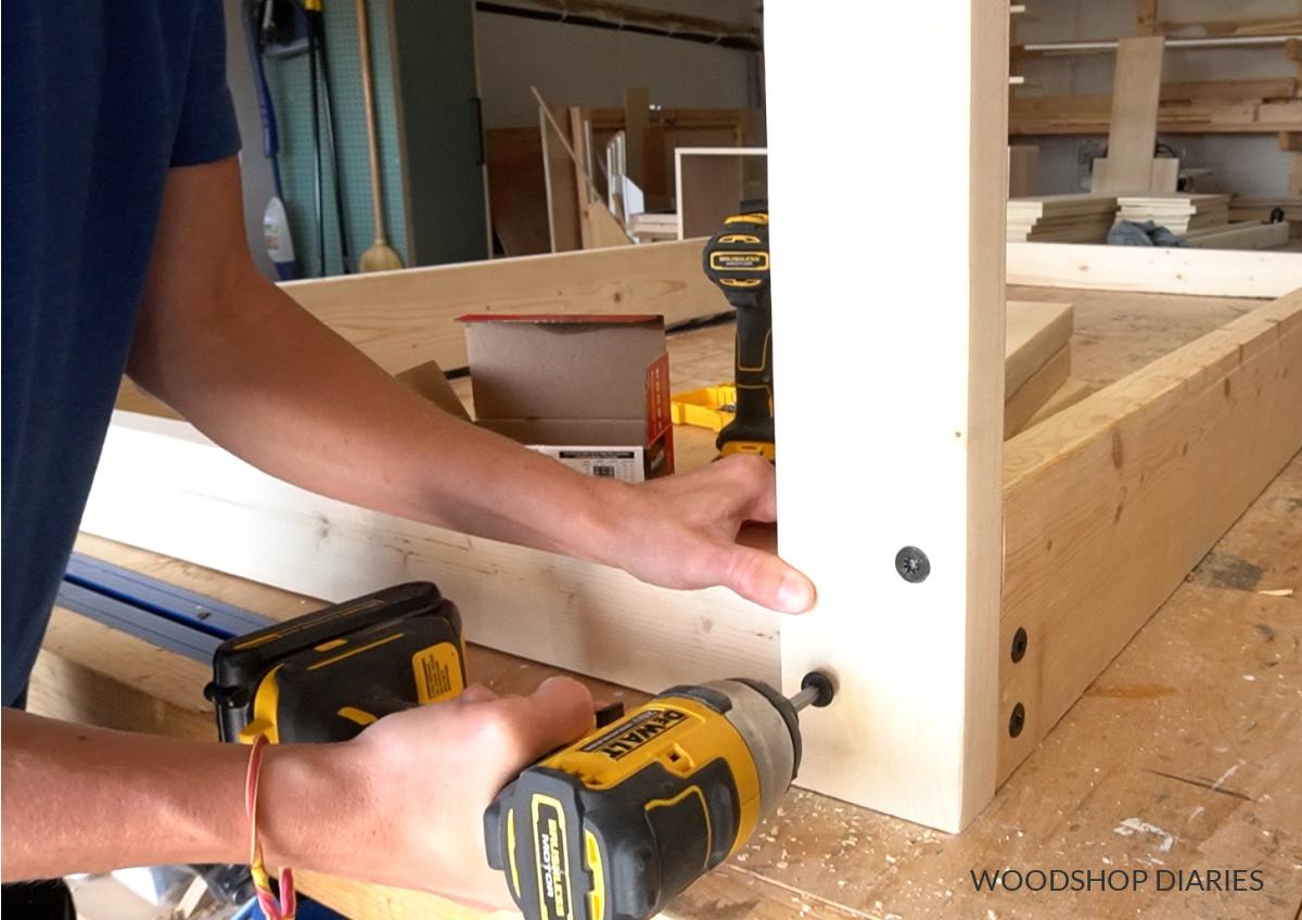 Close up of Shara Woodshop Diaries installing corner swing posts using timber screws