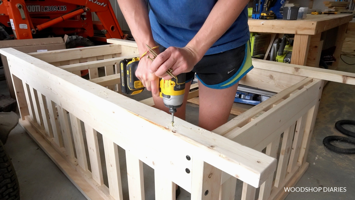 Shara installing bottom runners along front and back of swing frame using screws