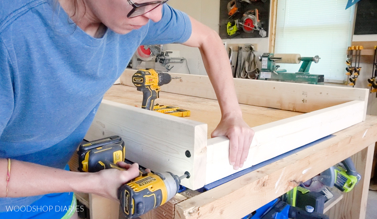 Close up of Shara Woodshop Diaries screwing swing bed seat frame together with timber screws
