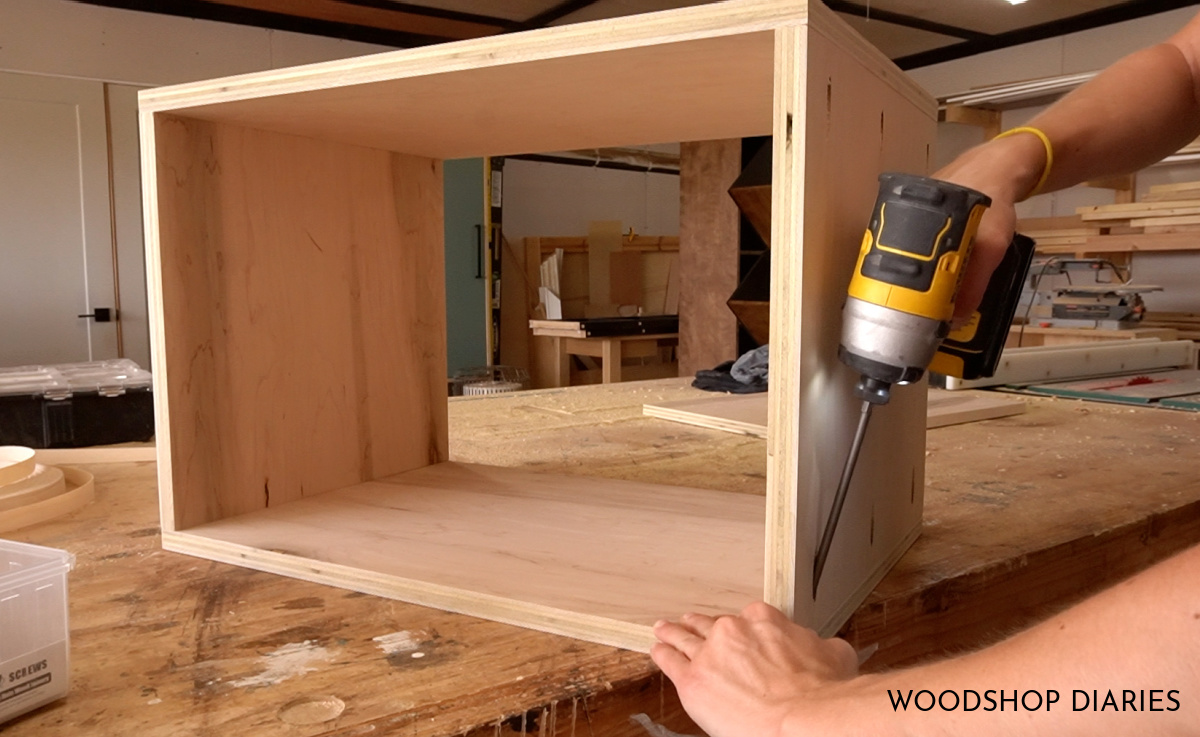 Shara Woodshop Diaries driving pocket hole screws to assemble inside nightstand box