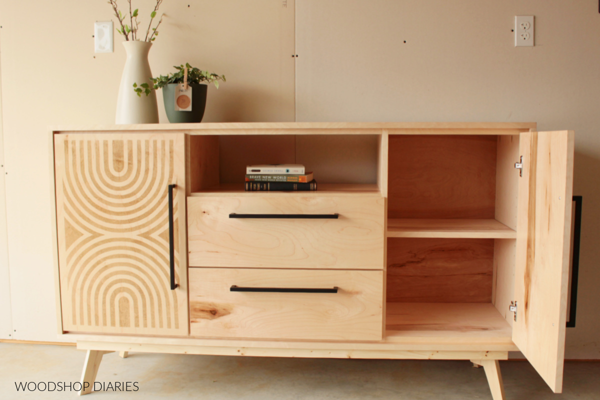 Finished DIY mid century modern dresser console with stenciled door open to show adjustable shelf