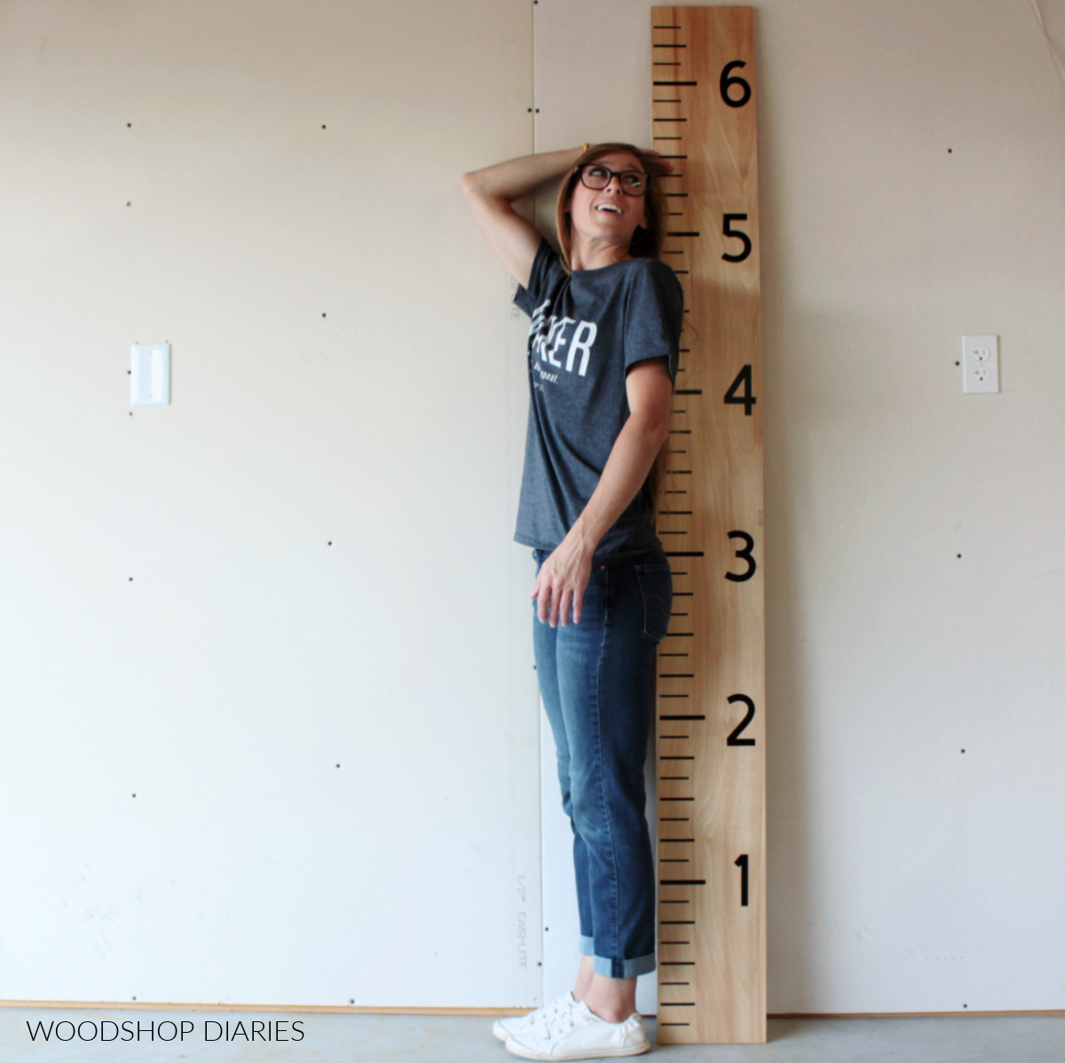 Shara Woodshop Diaries standing next to life size giant ruler board growth chart checking her height
