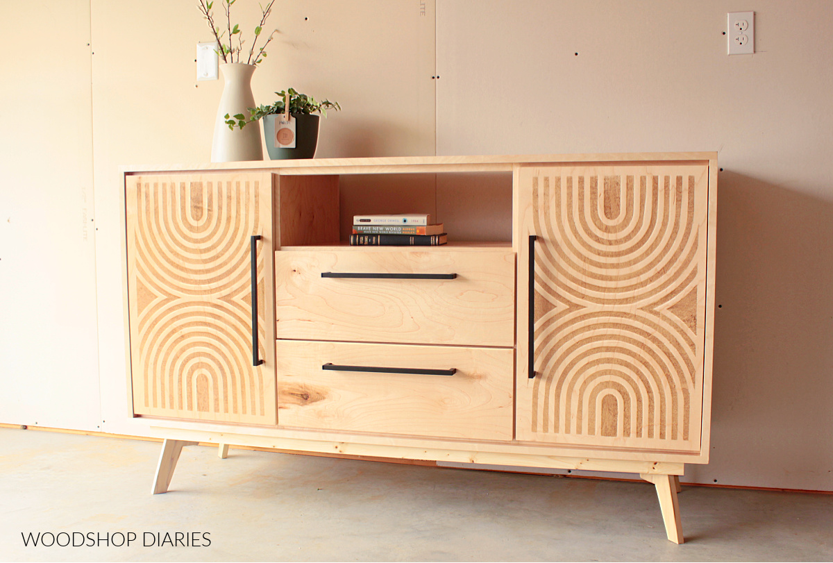 Maple mid century modern console cabinet with doors, drawers, and open shelf. Mid century stenciled doors on left and right