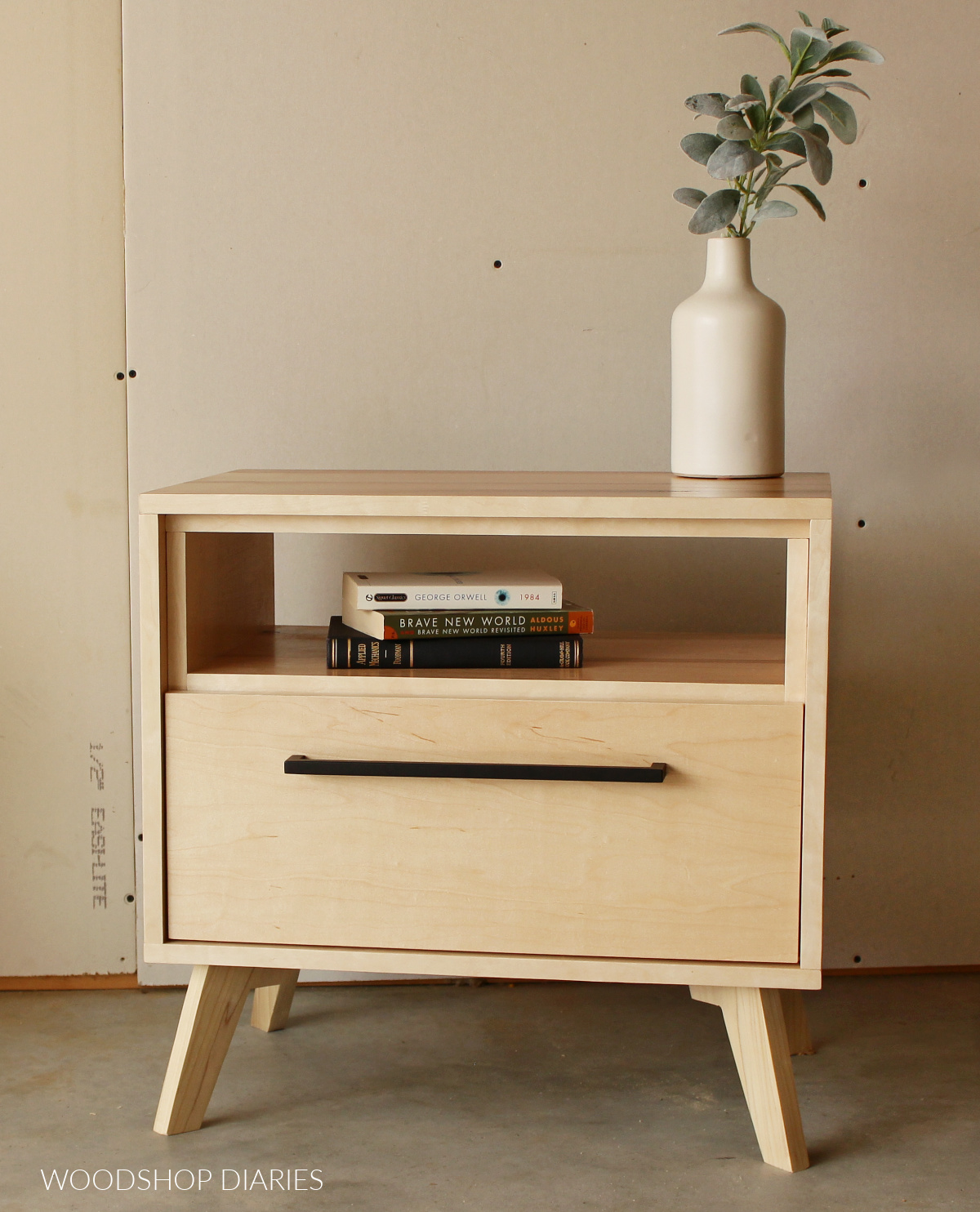 Finished nightstand--maple plywood finished with clear coat and a modern black handle on drawer.